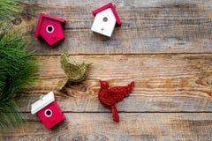 Decoraciones del Año Nuevo con el pájaro, los juguetes de la casa y el branche del árbol de navidad en mofa de madera del veiw de Imagenes de archivo
