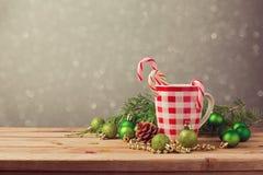 Decoraciones del día de fiesta de la Navidad con la taza y el caramelo comprobados en la tabla de madera Fotos de archivo libres de regalías