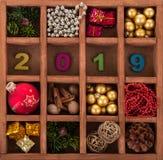 Decoraciones del día de fiesta para el árbol de navidad en la caja de madera y los números 2019 Fondo Fotografía de archivo