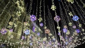 Decoraciones del invierno del Año Nuevo de la iluminación de la Navidad, noche que brilla la ciudad peatonal de la calle en el ce almacen de video