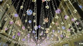 Decoraciones del invierno del Año Nuevo de la iluminación de la Navidad, noche que brilla la ciudad peatonal de la calle en el ce almacen de metraje de vídeo