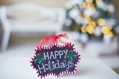 Decoraciones del invierno con buenas fiestas la muestra Imagen de archivo