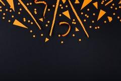 Decoraciones del partido de Halloween del confeti en la opinión superior del fondo negro estilo plano de la endecha foto de archivo