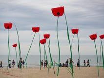 Decoraciones en la forma de amapolas gigantes en la costa en imagenes de archivo