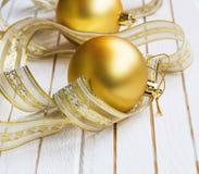 Decoraciones festivas de oro de las bolas de la Navidad con la cinta en blanco Imágenes de archivo libres de regalías