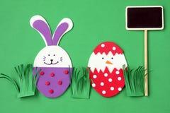 Decoraciones hechas a mano de Pascua: conejito festivo y huevo de la espuma plástica con la pizarra aislada en fondo verde Foto de archivo libre de regalías