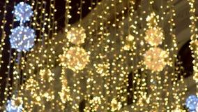 Decoraciones hermosas de oro del centelleo de las luces de la Navidad de la calle, fondo de la falta de definición almacen de video