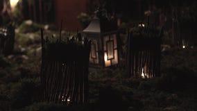 Decoraciones para el día de fiesta, pequeñas casas en la hierba, iluminada por las lámparas, en la noche metrajes