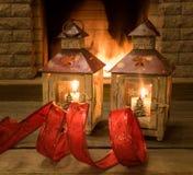 Decoraciones para la linterna de la Navidad, cinta roja en la tabla marrón vieja, antes de la chimenea acogedora imagen de archivo libre de regalías