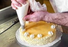 Decoraciones poner crema aflautadas del panadero en una torta Imagenes de archivo