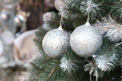 Decoraciones por Año Nuevo y días de fiesta Bolas de plata de la Navidad en ramas de árbol Fotografía de archivo