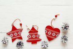 Decoraciones rojas de la Navidad con los conos del pino en los tableros blancos Tapa v Fotografía de archivo