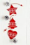 Decoraciones rojas de la Navidad con los conos del pino en los tableros blancos Tapa v Imagenes de archivo