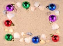 Decoraciones y conchas marinas coloridas de la Navidad en una arena de la playa Imágenes de archivo libres de regalías