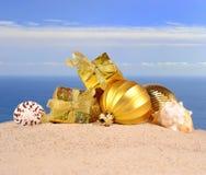 Decoraciones y conchas marinas de la Navidad en una arena de la playa Foto de archivo libre de regalías