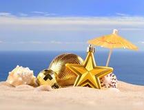 Decoraciones y conchas marinas de la Navidad en una arena de la playa Fotos de archivo libres de regalías