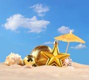 Decoraciones y conchas marinas de la Navidad en una arena de la playa Fotos de archivo