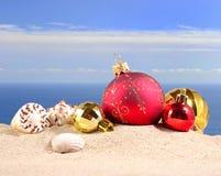 Decoraciones y conchas marinas de la Navidad en una arena de la playa Fotografía de archivo libre de regalías
