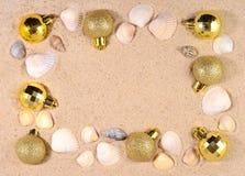 Decoraciones y conchas marinas de oro de la Navidad en una arena de la playa Foto de archivo libre de regalías