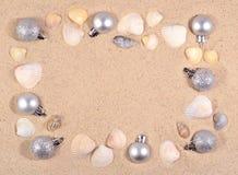 Decoraciones y conchas marinas de plata de la Navidad en una arena de la playa Fotos de archivo libres de regalías