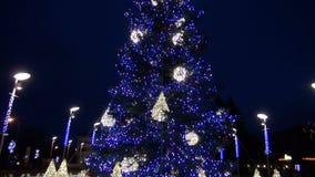 Decoraciones y luces del abeto del árbol de navidad del Año Nuevo en cuadrado de ciudad almacen de metraje de vídeo