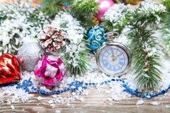 Decoraciones y reloj de la Navidad en la nieve Imagen de archivo libre de regalías