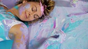 Decorado com a menina da ioga da pintura que coloca nela para trás na pintura vídeos de arquivo