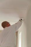Decorador casero que pinta una pared imagen de archivo