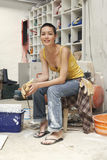 Decorador de interiores de sexo femenino que se sienta en taburete en sitio de trabajo fotos de archivo libres de regalías