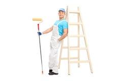 Decorador de sexo masculino joven que sostiene un rodillo de pintura fotografía de archivo