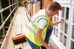 Decorador en el andamio que pinta la casa exterior Windows imagenes de archivo