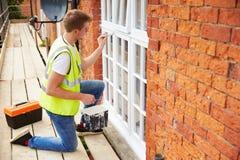 Decorador en el andamio que pinta la casa exterior Windows imágenes de archivo libres de regalías