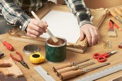 Decorador que barniza un marco de madera fotografía de archivo