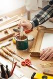 Decorador que barniza un marco de madera imagenes de archivo