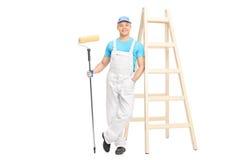 Decorador que sostiene un rodillo de pintura y que se inclina en la pared fotografía de archivo libre de regalías