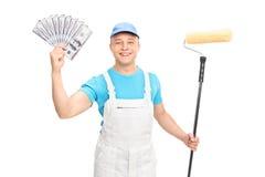 Decorador que sostiene un rodillo y un dinero de pintura foto de archivo