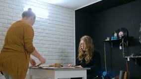 Decoradores de las mujeres profesionales, diseñadores que trabajan con el papel de Kraft almacen de metraje de vídeo