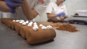 Decorando e producendo la patata del dolce di cioccolato Fabbrica della confetteria Il confettiere decora la crema del dolce, las stock footage