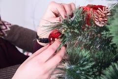 Decorando l'albero di Natale nel paese mano che tiene palla rossa Immagini Stock Libere da Diritti