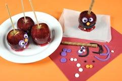 Decorando maçãs vermelhas do caramelo com as caras de sorriso loucas engraçadas para Dia das Bruxas Fotografia de Stock