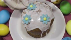 Decorando o bolo com açúcar colorido floresce para easter filme