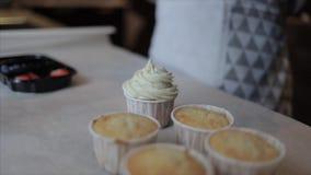 Decorando o bolo do copo com creme e morango, mirtilos e framboesa frescos filme