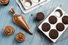 Decorando queques do chocolate com geada Imagem de Stock Royalty Free