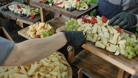 Decorando uma estação do queijo em um partido ou em um casamento incorporado Servi?o da restaura??o Estação com um grande queijo  vídeos de arquivo