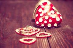 Decoração com corações e alianças de casamento vermelhos no backg de madeira Imagens de Stock Royalty Free