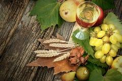 A decoração do outono com vinho e o outono orgânico frutificam Fotos de Stock Royalty Free