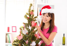 Decorate Christmas tree. Beautiful Asian woman decorating Christmas tree in her house Royalty Free Stock Images