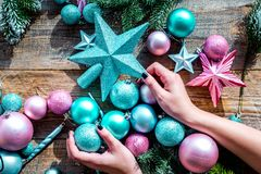 Decorate the christmas tree. Hands hold xmas toys. Stars and balls near pine branches on wooden background top view Stock Photography
