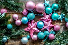 Decorate the christmas tree. Pink and blue stars and balls near pine branches on wooden background top view Stock Images