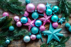 Decorate the christmas tree. Pink and blue stars and balls near pine branches on wooden background top view Stock Photography